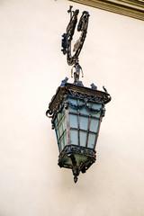 Old forged metal lantern on a wall closeup shot