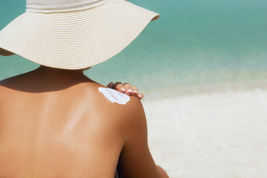 Woman applying sunscreen creme on  tanned  shoulder. Skincare. Body Sun protection suncream. Bikini hat woman applying moisturizing sunscreen lotion on back.