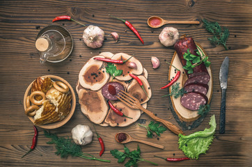 Sausage snag, pita bread, bagels, tomatoes, garlic, chilli pepper and greenery with fennels, dill and parsley on wooden table background.
