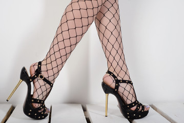 Seductive woman's legs wearing fishnet stockings and high heels