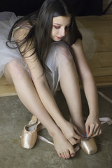 Young Ballet Dancer Putting on Pointe Shoes