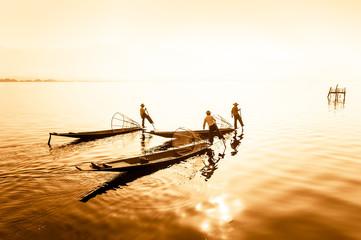 Burmese fisherman on bamboo boat catching fish. Myanmar