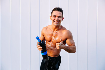 Smiling athlete man with biceps in earphones showing a thumb up looking at camera, holding a bottle of water. Outdoors.