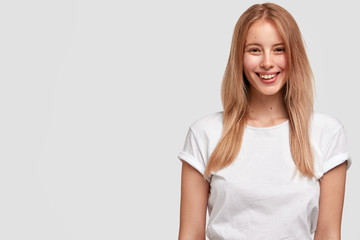 Wall Mural - Photo of happy young female freelancer with pleasant smile on face, wears white t shirt, happy to recieve bonus or promotion, stands against studio background with blank space for advertisement