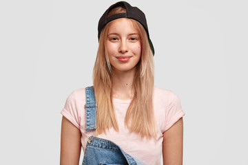 Pleased Caucasian teenage girl wears black cap and denim overalls, going to have stroll with friends, poses against white background. Youngster woman dressed in fashionable clothes. People and style
