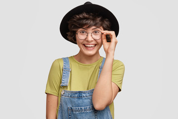 Indoor shot of good looking happy mixed race brunette female looks joyfully through round spectacles, dressed in fashionable dungaree and hat, stands against white background. Lovely cute student