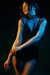 Sensual beautiful brunette woman in a sexy fashion dress colored with gems
