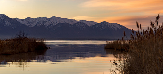 Panorama of a lake with mountains in the background during the golden hour