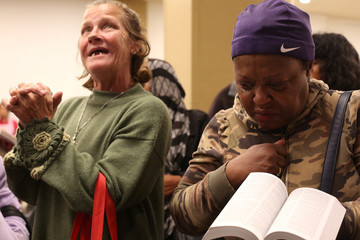 Lisa Maxwell and Judith Patterson pray during a religious service at a Mother's Day event for homeless and poor families at the Fred Jordan Mission, in Los Angeles