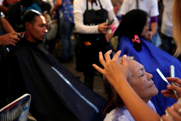 "A woman get her eyebrows trimmed by a volunteer of Venezuelan presidential candidate Javier Bertucci of the ""Esperanza por el Cambio"" party, during a campaign rally in Caracas"
