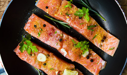 Salmon slices with cooking ingredients on a pan