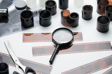Photonegatives, multiple films and magnifying glass on white background