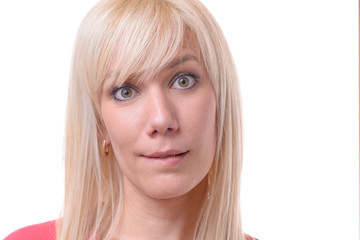 Quizzical blond woman biting her lip