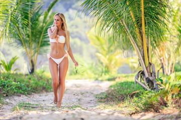 Woman in white bikini walking between palm trees at the tropical beach Wall mural