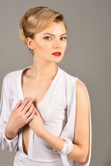 Skincare, haircare concept - elegant fashion woman retro style. Beautiful fashion retro girl with perfect fresh clean skin, red lips, bright makeup, retro hairdo. Sensual blonde model in white dress.