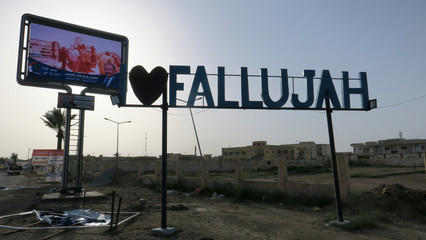 "A candidate's poster lies on the ground near an ""I love Falluja"" sign during an Iraqi parliamentary election in Falluja"