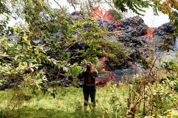Jolon Clinton, 15, takes photos as lava erupts from a fissure near her home east of the Leilani Estates subdivision during ongoing eruptions of the Kilauea Volcano in Hawaii