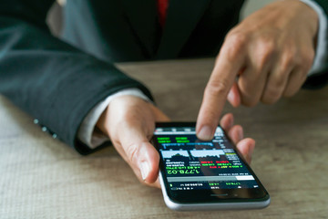 businessman using a mobile phone to check stock market data.