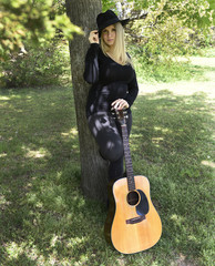 young woman playing guitar on park bench