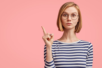 Portrait of serious stylish girl raises finger up, says: Attention please! Young stylish female teacher tries to explain something to pupils, has serious confident look, isolated on pink background