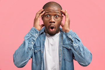 People, reaction, emotions and facial expression concept. Shocked African American male stares at camera with eyes popped out, forgets necessary information or thing, poses against pink wall