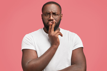 Horizontal portrait of handsome dark skinned plump male enterpreneur, being deep in thoughts, tries to find right solution in mind, wears casual white t shirt, isolated over pink background.