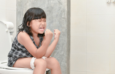 girl feel pain with constipation in the bathroom