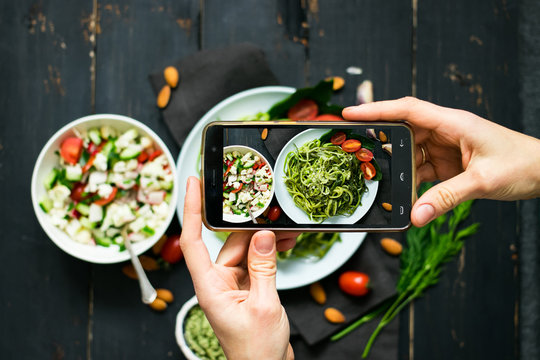 Phone photography of food. Woman hands take photo of lunch with smartphone for social media. Raw vegan zucchini spaghetti with avocado sauce. vegetarian healthy dinner