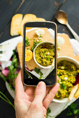 Phone photography of food. Woman hands take photo of lunch with smartphone for social media. Dip or spread. Raw vegan vegetarian healthy dinner