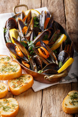 Copper pot of gourmet mussels with lemon, parsley and garlic served on a bread. vertical, rustic style