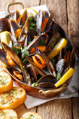 Mussels in wine with parsley and lemon. Seafood. Clams in the shells. Delicious snack for gourmands. vertical, rustic style
