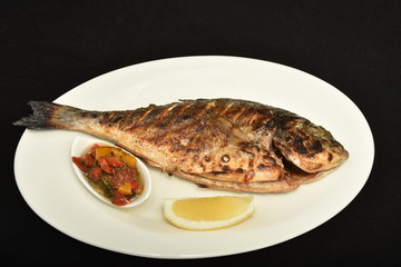 Barbecue scene, Whole fish garnished with lemon, fresh off the grill.