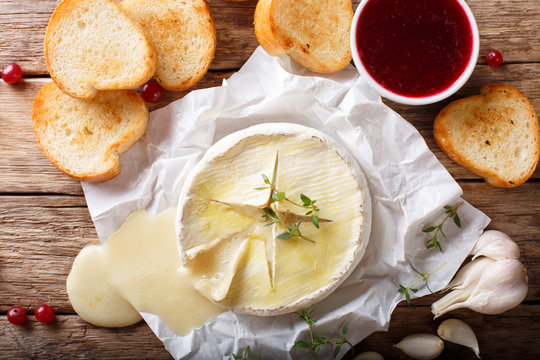baked camembert cheese with thyme and garlic served with roasted bread close-up. horizontal top view