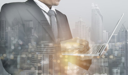 Multiple exposure of business man is using laptop with city skyline as for business background.