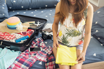 Young woman traveler packing her clothes and stuff in suitcase, Travel and vacation concept