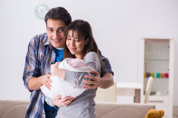 Young parents with their newborn baby near bed cot