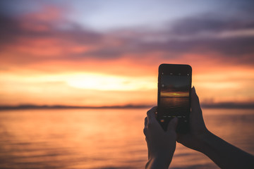 people take a photo of  dramatic sky sunset time golden hour