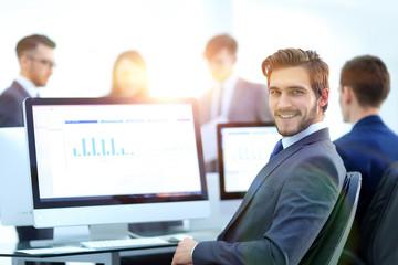 Businessman analyzing economic graphs at office