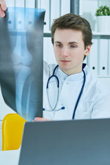 Close up portrait of young male doctor holding x-ray or roentgen image.