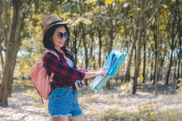beautiful woman traveler smiling be happy backpacking and holding map under the trees ready to go to hiking travel walking in to forest. holiday adventure trekking and camping relax outdoor concept.