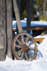 старое деревянное колесо на фоне снега и деревянного забора