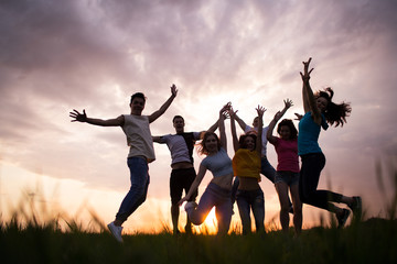 Young people jumping against the sunset sky