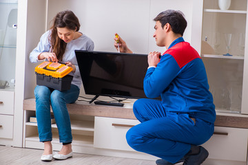 Repairman repairing tv at home