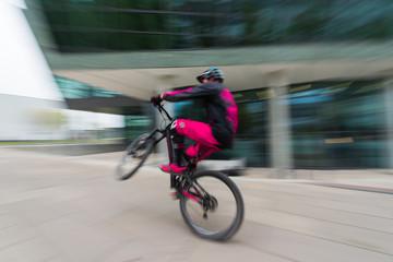Sportlicher Radfahrer in der Innenstadt mit Bewegungsunschärfe