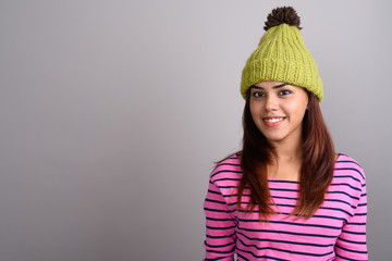 Young beautiful Indian woman wearing knitted hat against gray ba