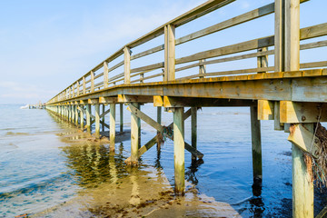 Borstahusen, Sweden - The underside of a wooden pier with logs driven into the sea bottom. Shallow water on a calm and windless day.