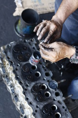 dirty, greasy Asian man's hands, oiling and greasing valves and pistons and inserting into an engine block in a dirty workshop in Thailand, Southeast Asia