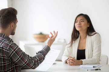 Disgruntled employee or angry client complaining on bad contract demanding compensation at meeting with asian lawyer, disagreeing with chinese partner listening claims about document, fraud concept