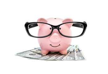 Piggy bank in glasses with money on white background.