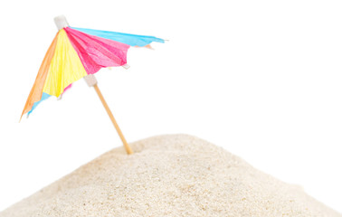 Small decorative parasol on heap of sand. Isolated on white.